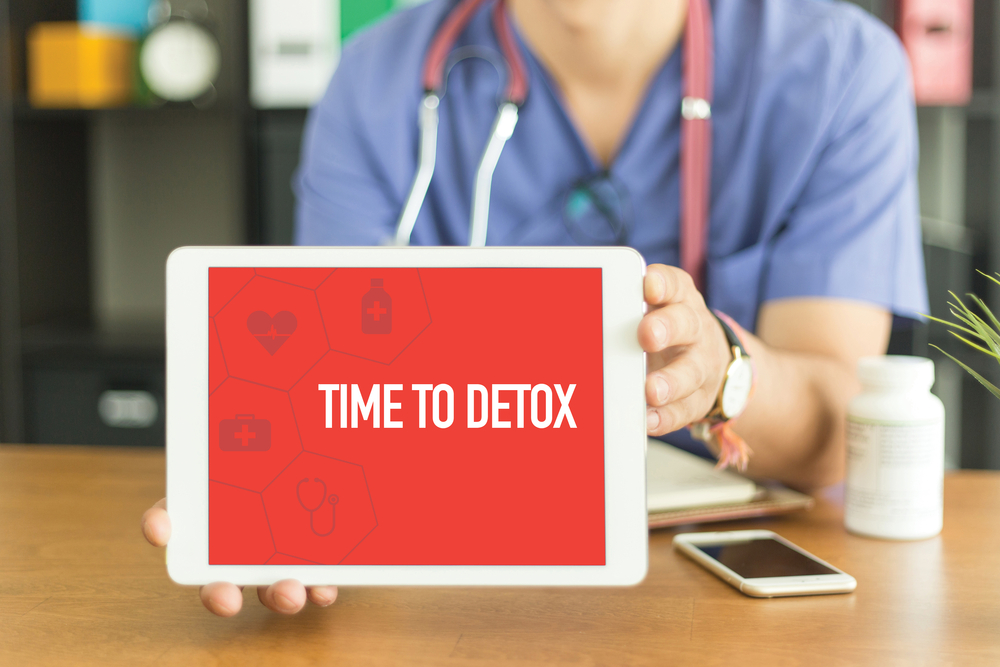 Nurse holding a laptop saying time to detox