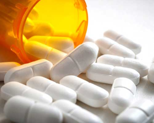 opioid-pills-spilling-out-of-bottle