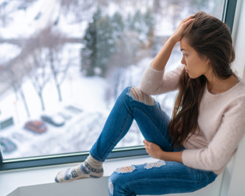 woman-with-sad-looks-out-window-to-wintery-day