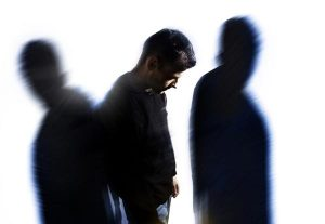 Man looking at the ground, surrounded by shadowy figures