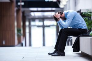Stressed man in business clothing grabbing his head while bent over on a chair