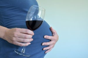 Pregnant woman holding her stomach and a glass of wine