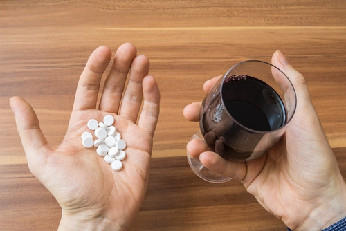 white pills and wine in each of a persons hands