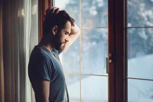 Tired man gazing out of window