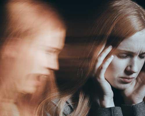 woman having panic attack on black background