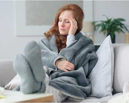 woman-on-couch-experiencing-headache-from-adderall-withdrawal-symptoms