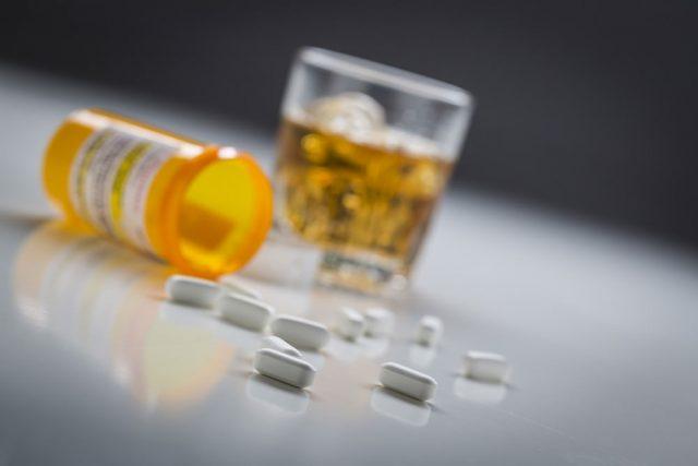 spilled prescription pills and bottle next to a glass of dark liquor