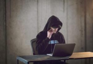 Man in hoodie looking at his laptop