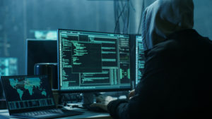 Hooded hacker with multiple monitors