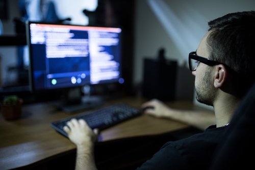 Picture of a man on his computer with the screen blurred out.