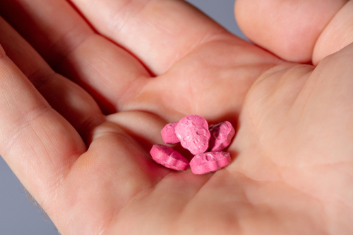 Pink ecstasy pills in a palm