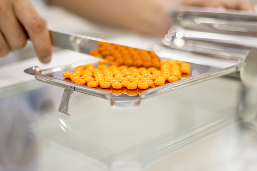 Orange pills on a counting tray