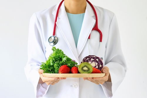 Doctor holding a plate of food and vegetables