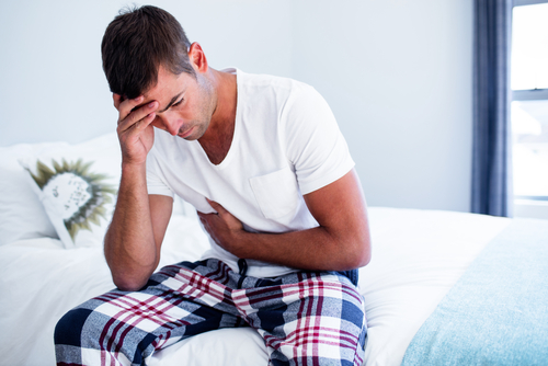 Man with stomach discomfort sitting on the end of his bed