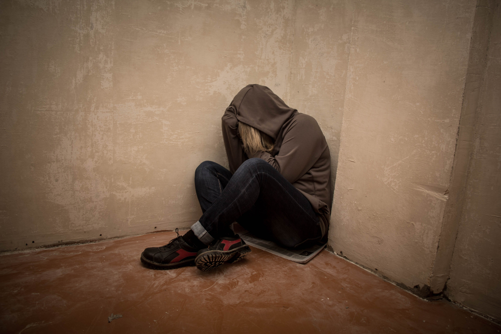 depressed fentanyl addicted man in hoodie in dark room