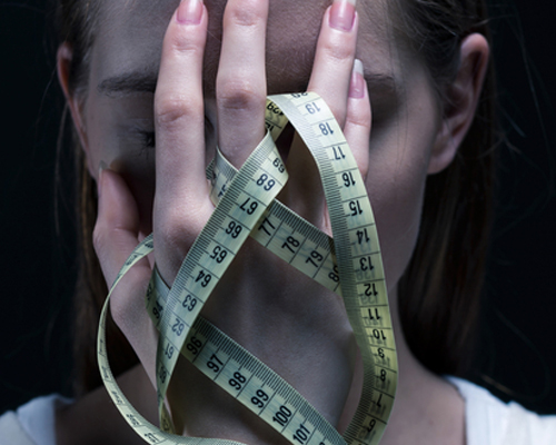 young-distraught-girl-with-an-eating-disorder-holding-measuring-tape