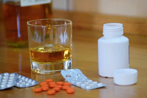 A glass of whiskey next to orange pills