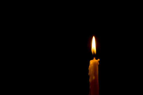 A single lit candle in the dark