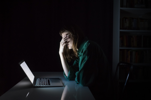 Stressed woman pinching her forehead in front of a laptop in a dark room