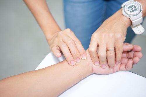 A nurse taking a patient's pulse on their wrist.