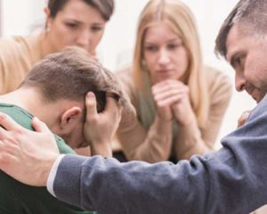 A circle of people consoling a man with his head down