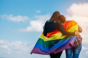 Two women wrapped in a gay pride flag