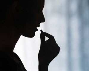 Silhouette of a woman eating a pill