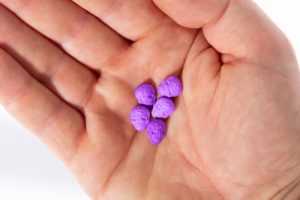 Purple ecstasy pills in a palm